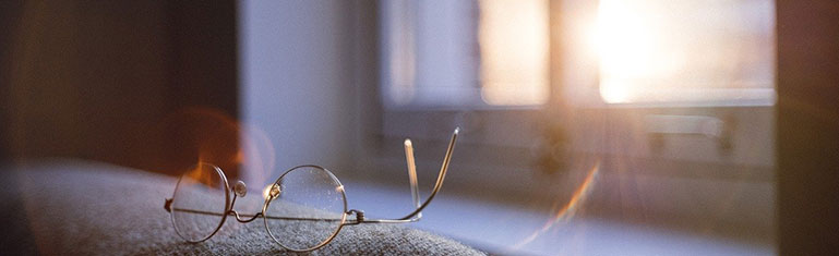 Glare from the sun streams in through a window and falls on a pair of eyeglasses.