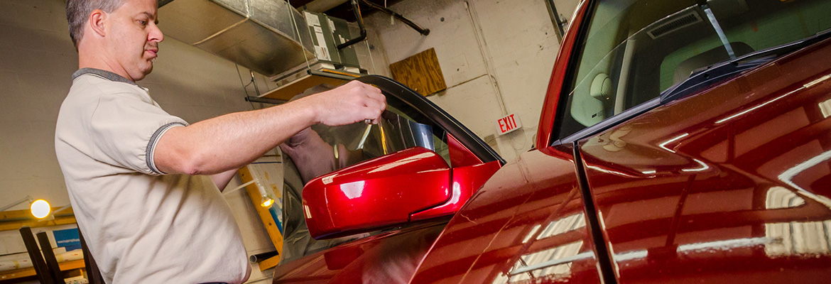 Suntamers employee applying automotive window tint to a customer vehicle